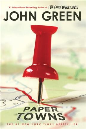photograph of large red thumb tack pressed into road map